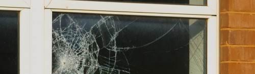 Een gebroken raam, dat vraagt om glasherstel in Arnhem